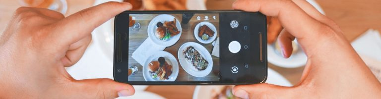 a person taking a photo of a table with food on it